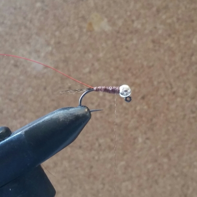 Now I switch bobbins to the Nymph-It and create the body in touching turns towards the bend. I don't mind gaps here but the more anal fly tier may want to take their time here. On the way back up the shank I use the Nymph-It to create a rib for the wire to follow. Tie off with Nymph-It with a couple of whip finishes - apply some varnish again if you like.